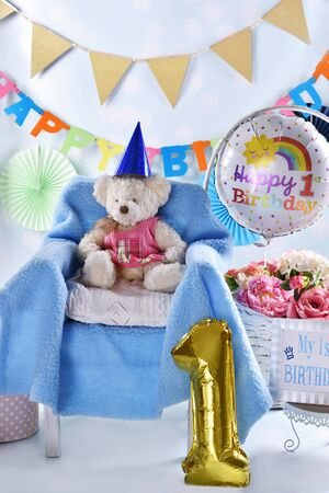 colorful happy first birthday background or card with teddy bear sitting on the armchair, balloons and flowers