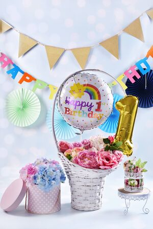 colorful happy first birthday background or card with balloons and flowers Banco de Imagens