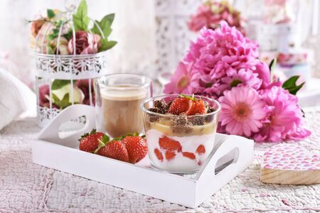 healthy diet breakfast is a wooden tray with yogurt, fresh strawberries, heart shaped granola and coffee
