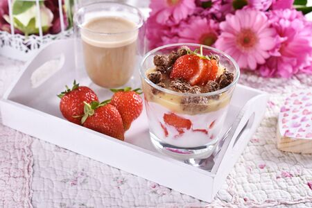 healthy diet breakfast to bed on wooden tray with yogurt, fresh strawberries, heart shaped granola and coffee