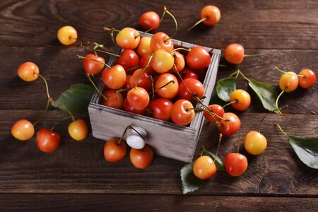 fresh yellow and red sweet cherries flat lay on wooden table Banco de Imagens