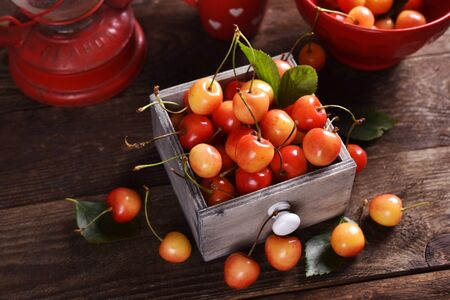fresh yellow and red sweet cherries still life on wooden table