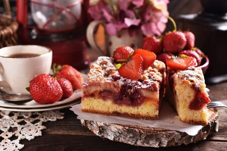 homemade strawberry cake and a cup of coffee on the table in rustic style