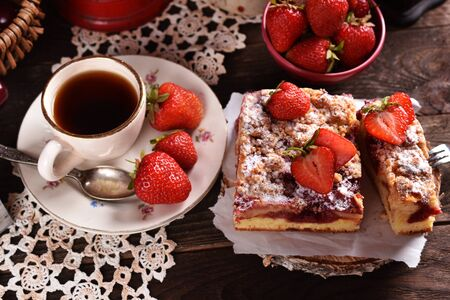 homemade strawberry cake and a cup of coffee on the table in a rustic style-top view