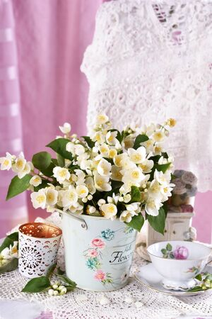bunch of fresh jasmine flowers standing on the chair in vintage style interior Banco de Imagens