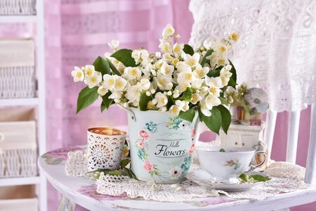 bunch of fresh jasmine flowers standing on the chair in vintage style interior