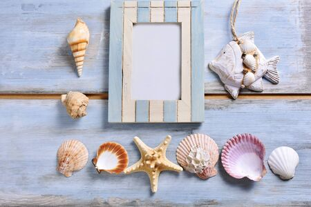 summer holidays flat lay with old photo frame and shells lying on blue wooden background