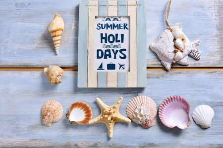 summer holidays flat lay with old photo frame with inscription and shells lying on blue wooden background