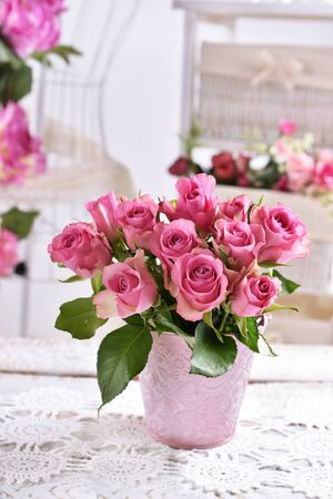 beautiful bunch of fresh pink roses in vase standing on the table
