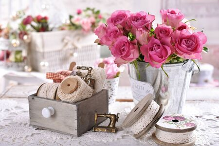 vintage style still life with cotton lace trims on wooden spools and bunch of pink roses on the table