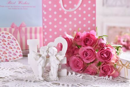 beautiful white decor with kissing angels and LOVE letters  in front of gift bags and roses Banco de Imagens