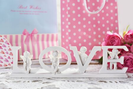 beautiful white decor with LOVE letters and angels in front of gift bags and roses