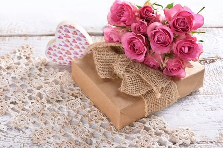 love background with gift box and bunch of pink roses lying on the table Banco de Imagens