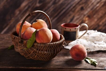 fresh ripe peaches in a wicker basket on rustic style wooden table Banco de Imagens