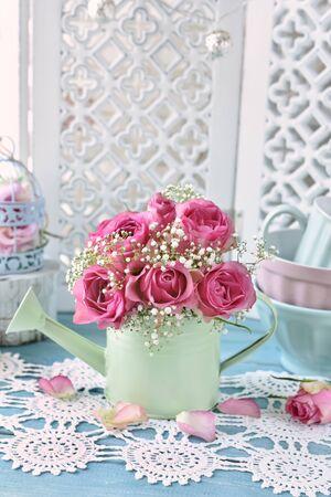 bukiet różowych róż w miętowej konewce we wnętrzu w stylu shabby chic