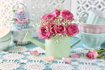 bunch of pink roses in a mint watering can in shabby chic style interior