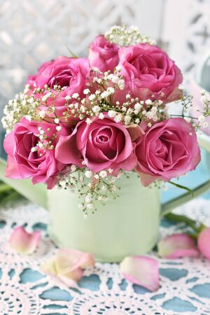 bunch of pink roses in a mint watering can in shabby on the table