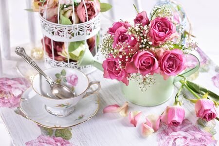 romantic style still life with bunch of pink roses, teacup and decors in pastel colors