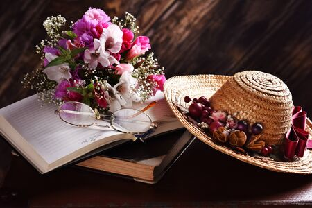 rural summer still life with straw hat, books, bunch of flowers lying on old suitcase in the dark interior Banco de Imagens