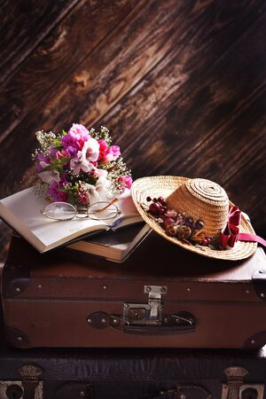 rural summer still life with straw hat, books, bunch of flowers lying on old suitcases in the dark interior