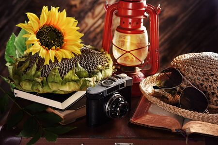 retro style summer trip still life with old camera, a straw hat, sunflower, books and oil lamp lying on suitcase