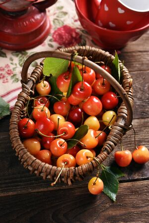wicker basket full of yellow and red cherries on rustic wooden table-top view