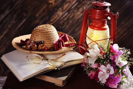 rural summer still life with straw hat, books, bunch of flowers and oil lamp burning in the dark