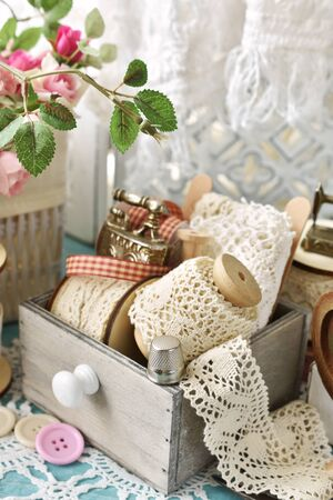 vintage style sewing kit and wooden spools with lace trims on the table