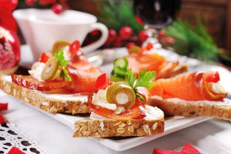christmas canapes with salmon cones filled with cheese and olives on festive table