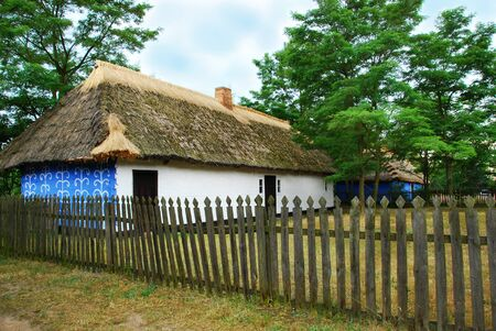 traditional village cottage with thatched roof and walls painted on white and blue with wooden fence