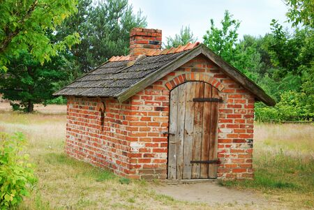 old village brick pantry building with wooden doors Stock Photo