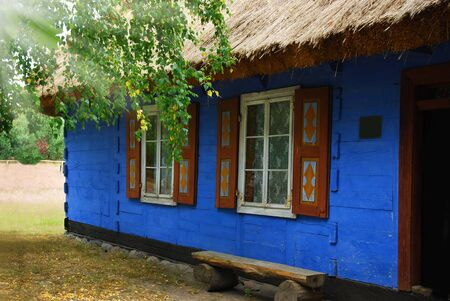 traditional village cottage with thatched roof and walls painted on blue with wooden shutters