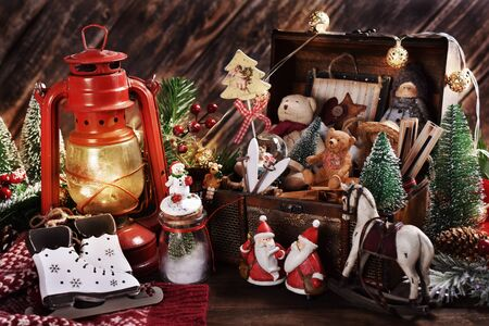 vintage style Christmas decoration with old toys and decors in wooden treasure chest and oil lamp