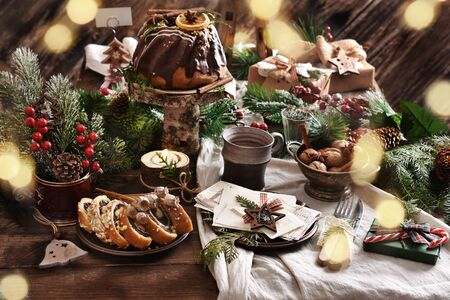 rustic style wooden table with Christmas Eve wafer, traditional cakes, decors and bokeh lights