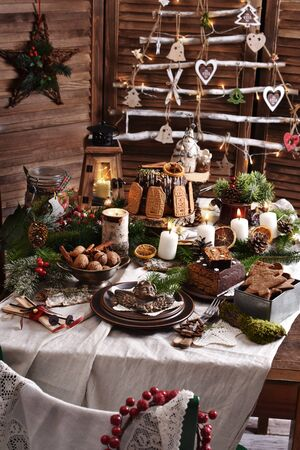 Christmas table setting in rustic style with gingerbread cake and cookies, ring cake, fir and eco decors on linen tablecloth