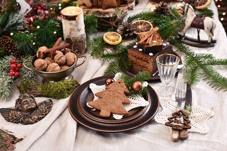 Christmas table setting in rustic style with gingerbread cake and cookies, fir and eco decors on linen tablecloth