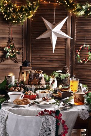 traditional Polish Christmas Eve dished and pastries on festive table in rustic style interior