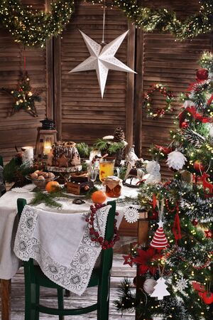 Christmas table setting with traditional cakes and decors in rustic style interior with Christmas tree