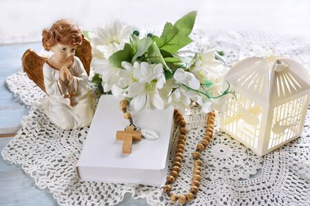 First Holy Communion still life with prayer book, rosary, angel and floral wreath