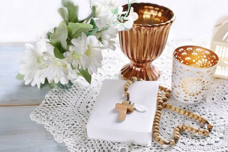 First Holy Communion background with prayer book, rosary, floral wreath and golden chalice