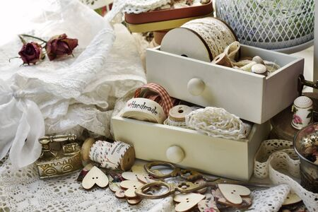 sewing supplies like wooden buttons, lace trims, scissors and ribbons in vintage style