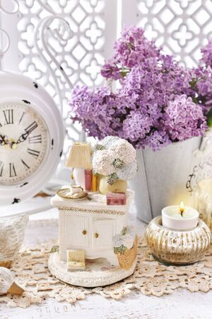 vintage style home decoration with bunch of purple lilac blossoms and old clock standing on the chest of drawers
