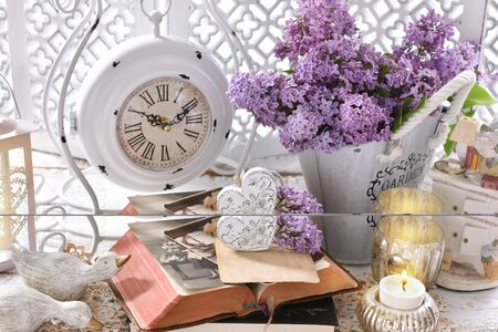 vintage style home decoration with bunch of purple lilac blossoms, books, photos and old clock standing on the chest of drawers 免版税图像