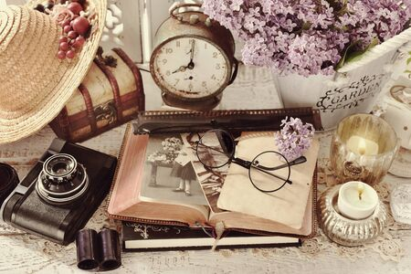 vintage style still life with old photographs, camera, films, clock, hat and wooden chest 免版税图像