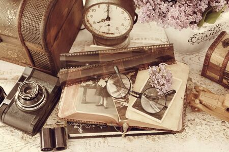 vintage style still life with old photographs, camera, films, clock and wooden chests