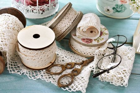 vintage style sewing supplies, spools of lace trims, old scissors and glasses on wooden table