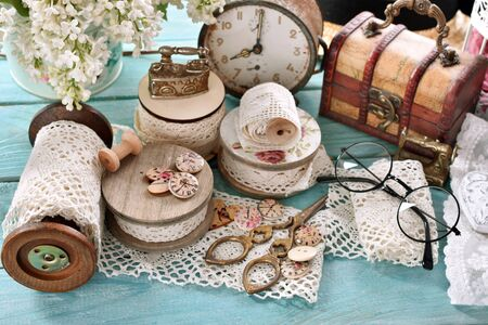 vintage style sewing supplies, spools of lace trims, old scissors and buttons on wooden table