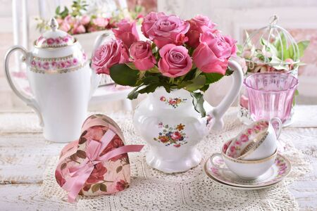 bouquet of pink roses in porcelain jug on the table with heart shaped gift box and porcelain in shabby chic interior