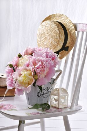 bouquet of fresh pink peonies in metal basket standing on the chair in vintage style