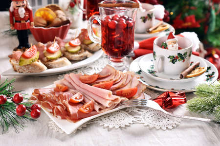 Christmas table with platter of sliced ham and meats and mini canapes with parma ham